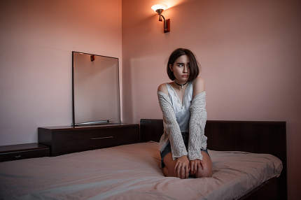a young girl in a short skirt and a white blouse sits on the bed