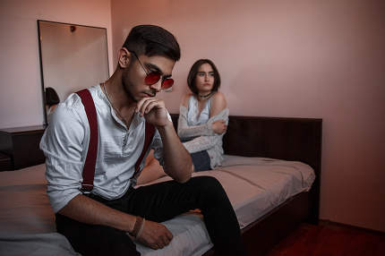 a young stylish guy in glasses sits on the edge of the bed with