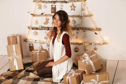 Beautiful smiling girl holding big Christmas gift over white backgound