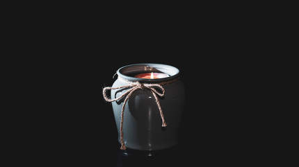 Candle burns in a vase on an isolated black background