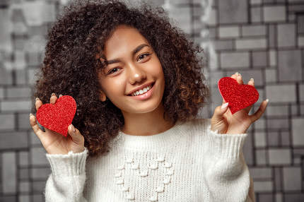 close-up portrait of a young curly-haired African American girl in a white sweater holding two paper hearts .  shallow depth of focus