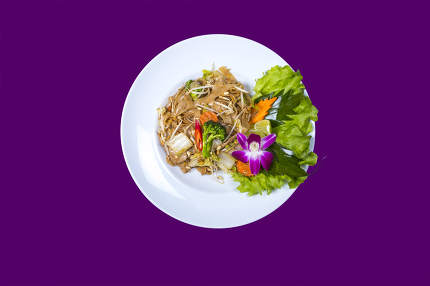 cooked noodles on a white plate and purple background