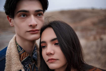 Dramatic portrait of a young brunette girl and a guy in cloudy weather.the girl leaned over the boy