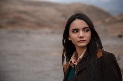 Dramatic portrait of a young brunette girl in cloudy weather against the background of mountains. selective focus, small focus area