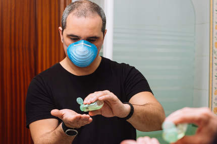 man with face mask applying disinfectant sanitizer onto hand for