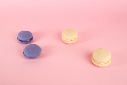 multicolored macaroni cookies on pink isolated background