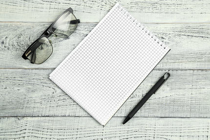 paper notebook with ballpoint pen and optical glasses on wooden