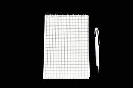 paper notebook with ballpoint pen on black isolated background