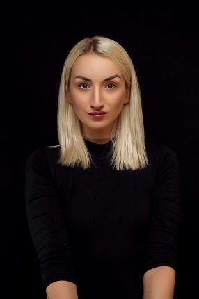 portrait of a young beautiful blonde woman in black clothes on a black isolated background