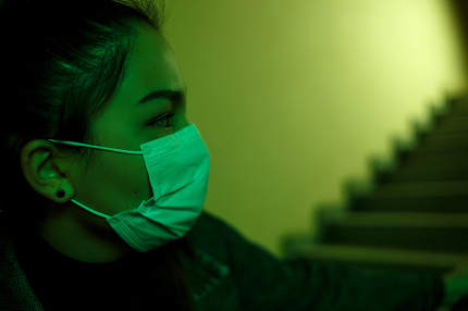 portrait of an Asian young woman in a disposable medical mask. stairwell of the hospital. the girl looks back anxiously. fear