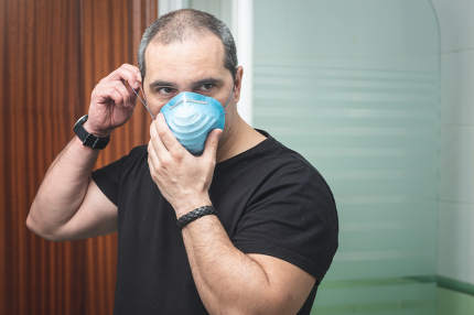 Portrait shot of an man putting a protective mask to avoid the s