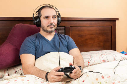 sick man with headphonelaying videogames in the bed