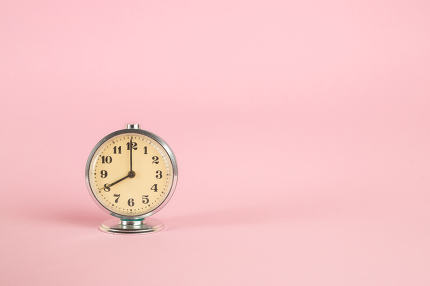 small vintage retro alarm clock on pink isolated background