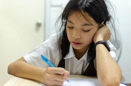 Students intending homework at the table
