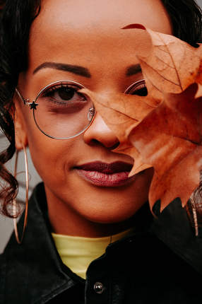 Woman with one eye covered by an Autumn leaf