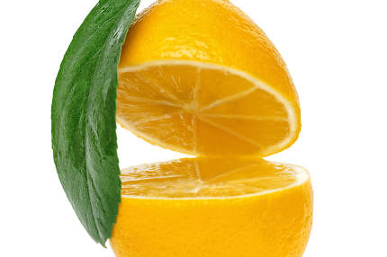 yellow lemon cut into two parts with a leaf isolated on a white background