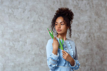 Young African girl in a blue dress with a Tulip on a gray background. The concept of women