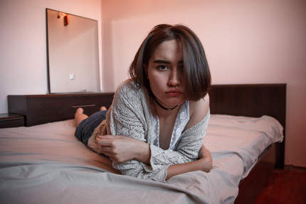 young girl with short hair in a sweater, denim skirt lying alone