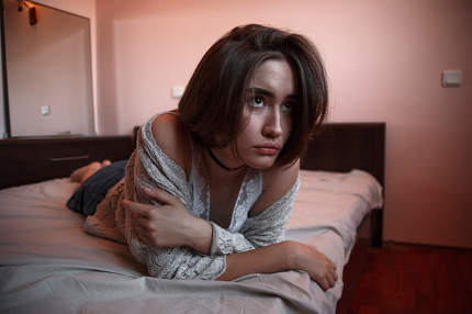 young girl with short hair in a sweater, denim skirt lying alone. depression
