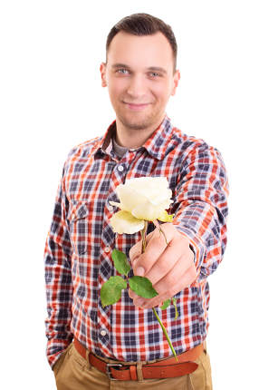 Young man handing out a white rose flower