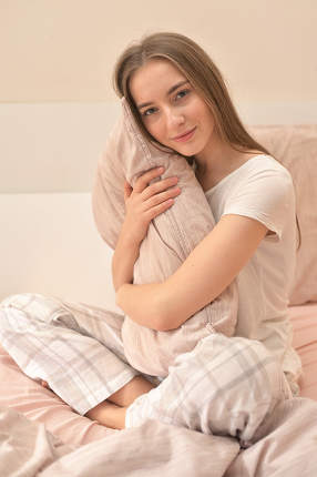 Young Woman With Pillow On Bed In Bedroom