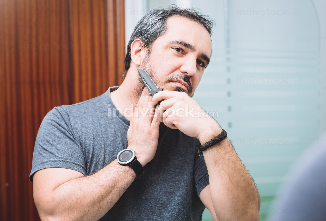 40s man shaving with sharp hunting knife