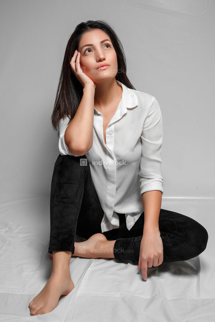 a brunette woman in a white shirt and black leggings sits on a w