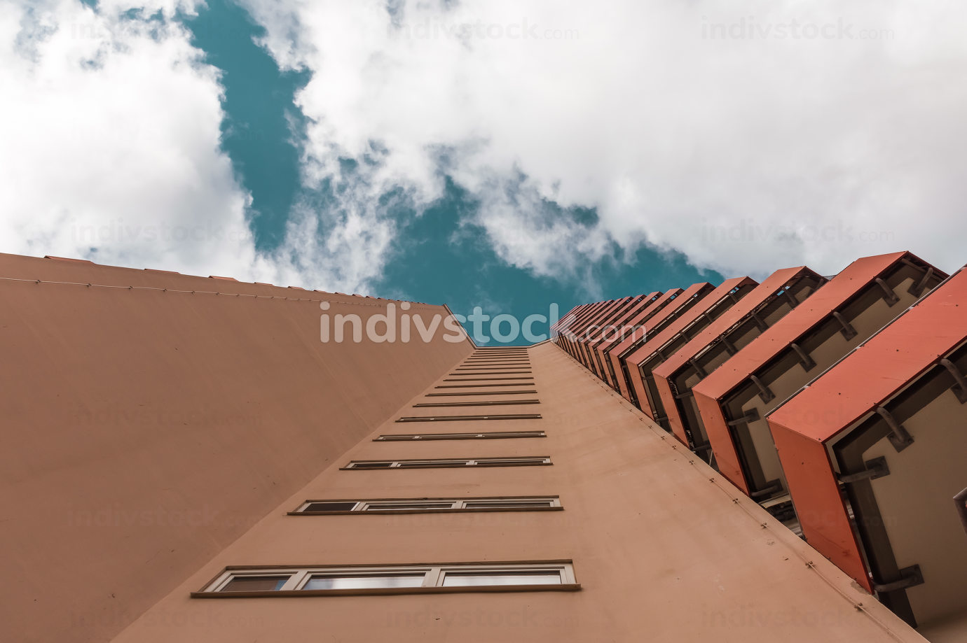 a high-rise with small red balkons with a view from below