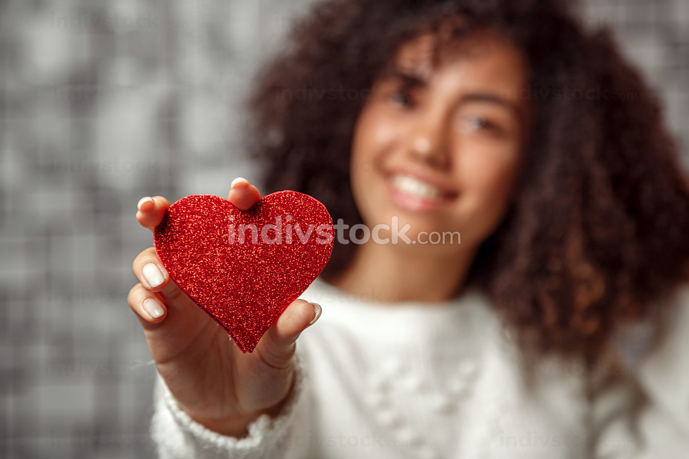 a paper red heart in  hands of a young African American curly-haired girl. focus on the heart, shallow depth of focus