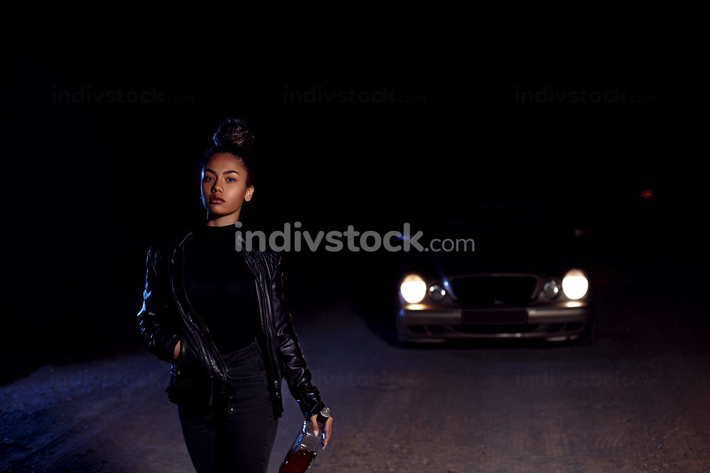 a young African-American mulatto girl in a leather jacket and black clothes is walking road