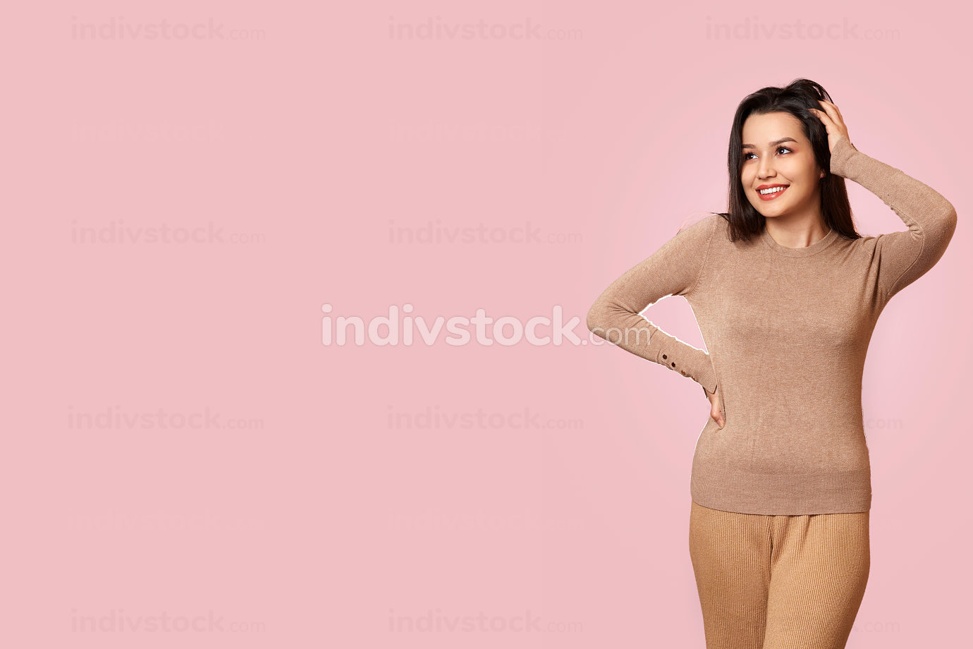 a young beautiful brunette girl in a light brown jacket laughs. on a pink isolated background