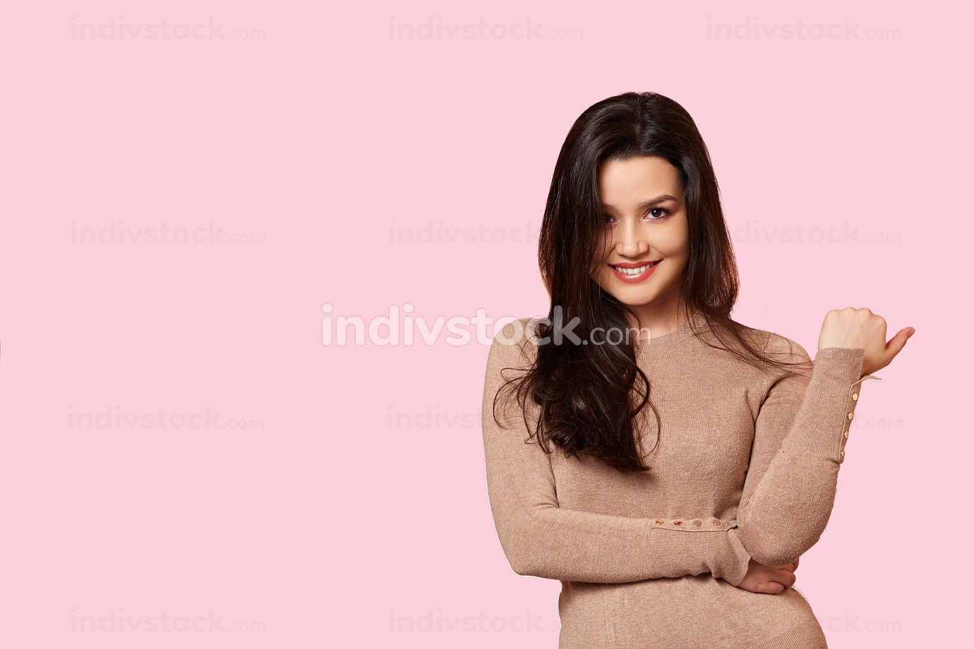 a young beautiful brunette in a light brown sweater is smiling. on a pink isolated background