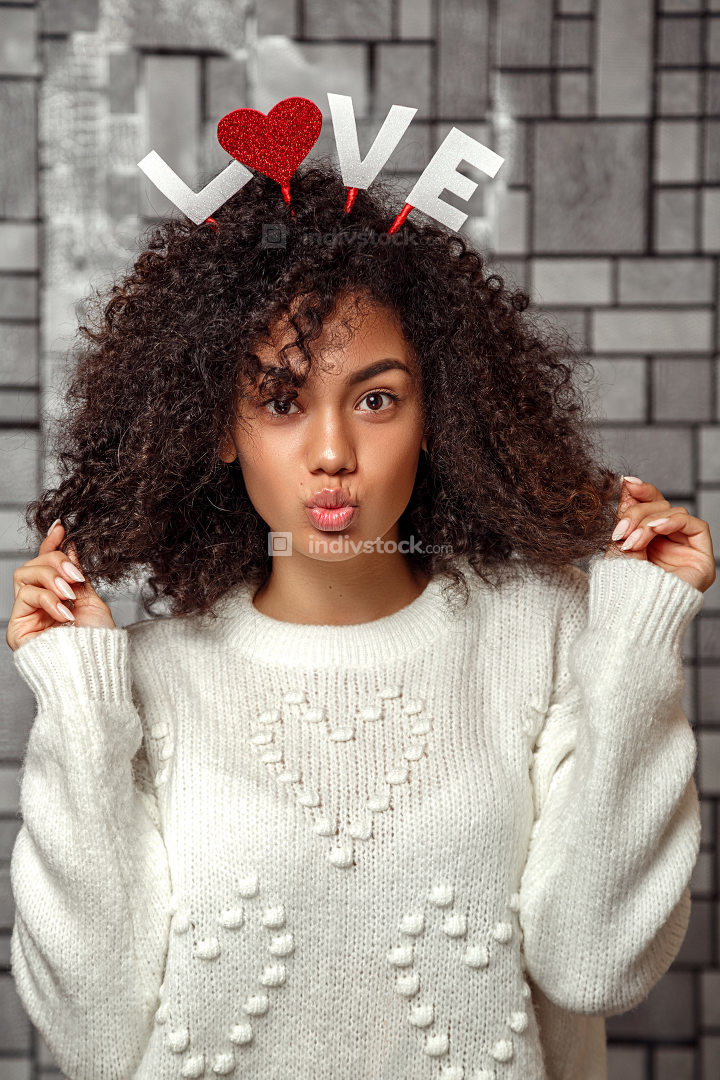 a young beautiful curly haired girl with a rim with the inscription love on her head makes a kiss with her lips