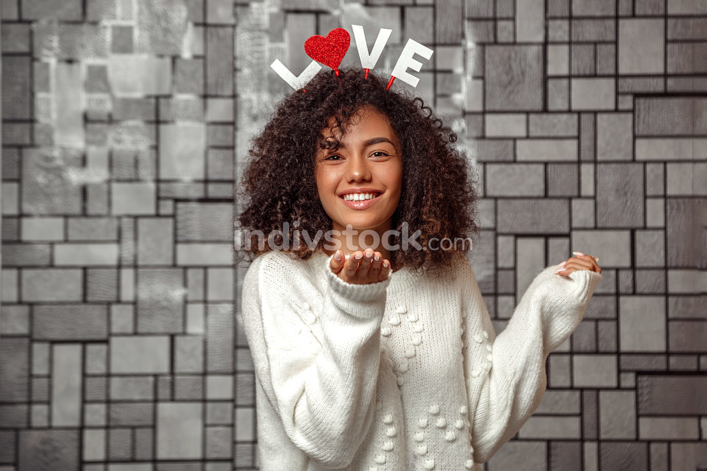 a young beautiful curly haired girl with a rim with the inscription love on her head sends a kiss through the air .Emotions and pleasant feelings concept.