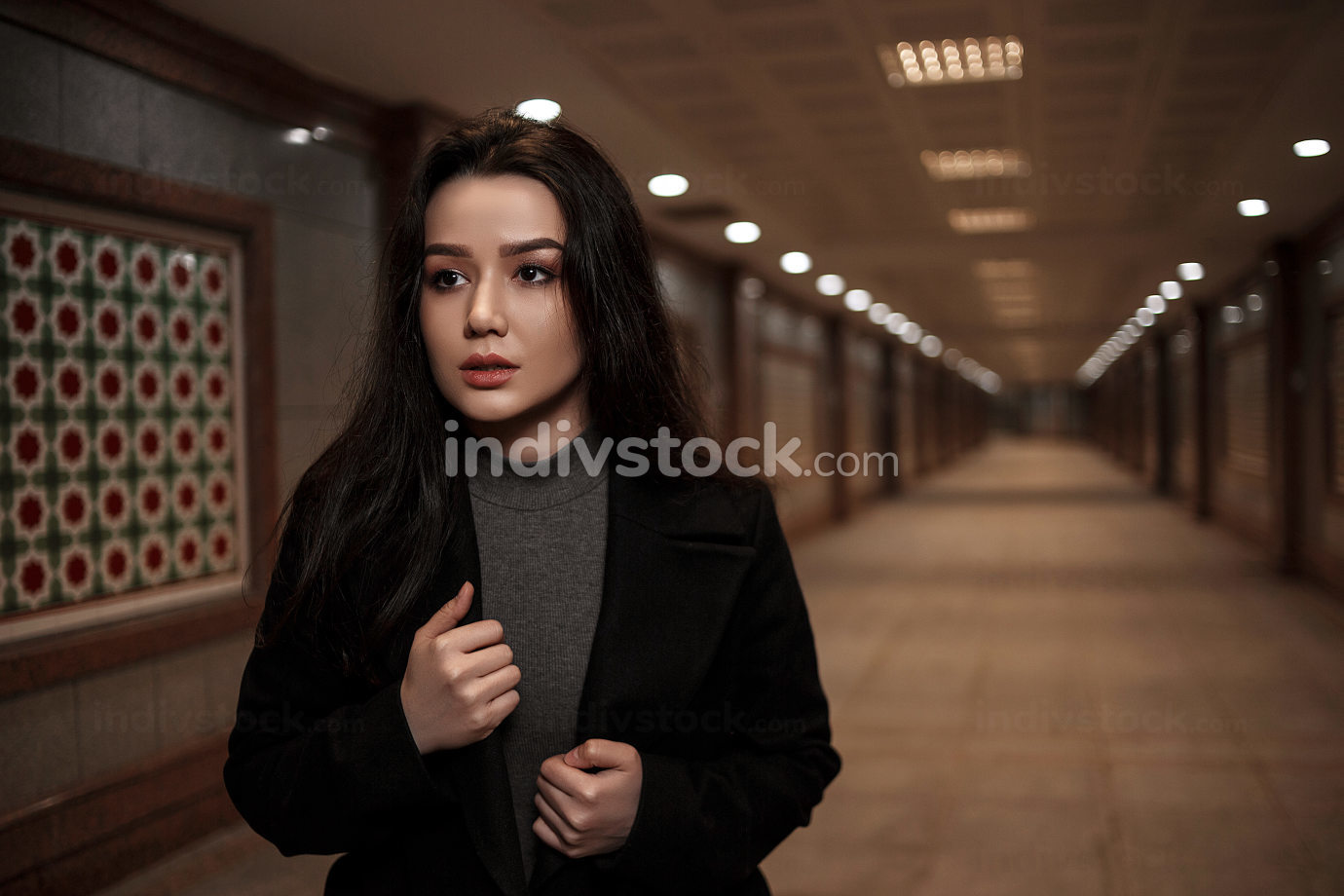 a young, beautiful woman walks through an underpass at night, looking back uneasily