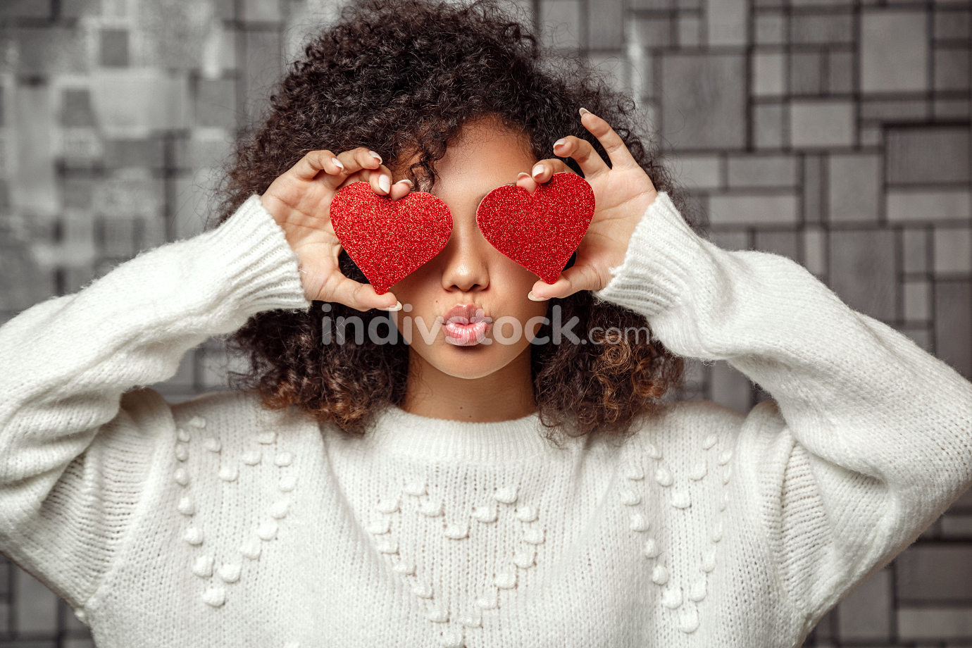 a young curly-haired African American girl in a white sweater holds two hearts in her hands . closes eyes with hearts and makes a kiss