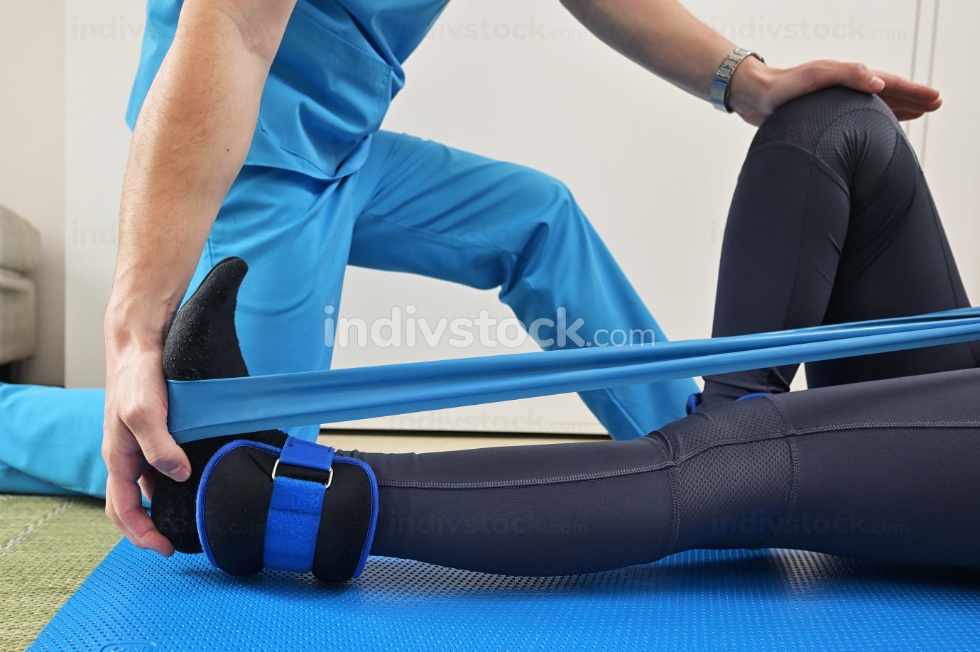 A young male physiotherapist helping a girl with stretching exer