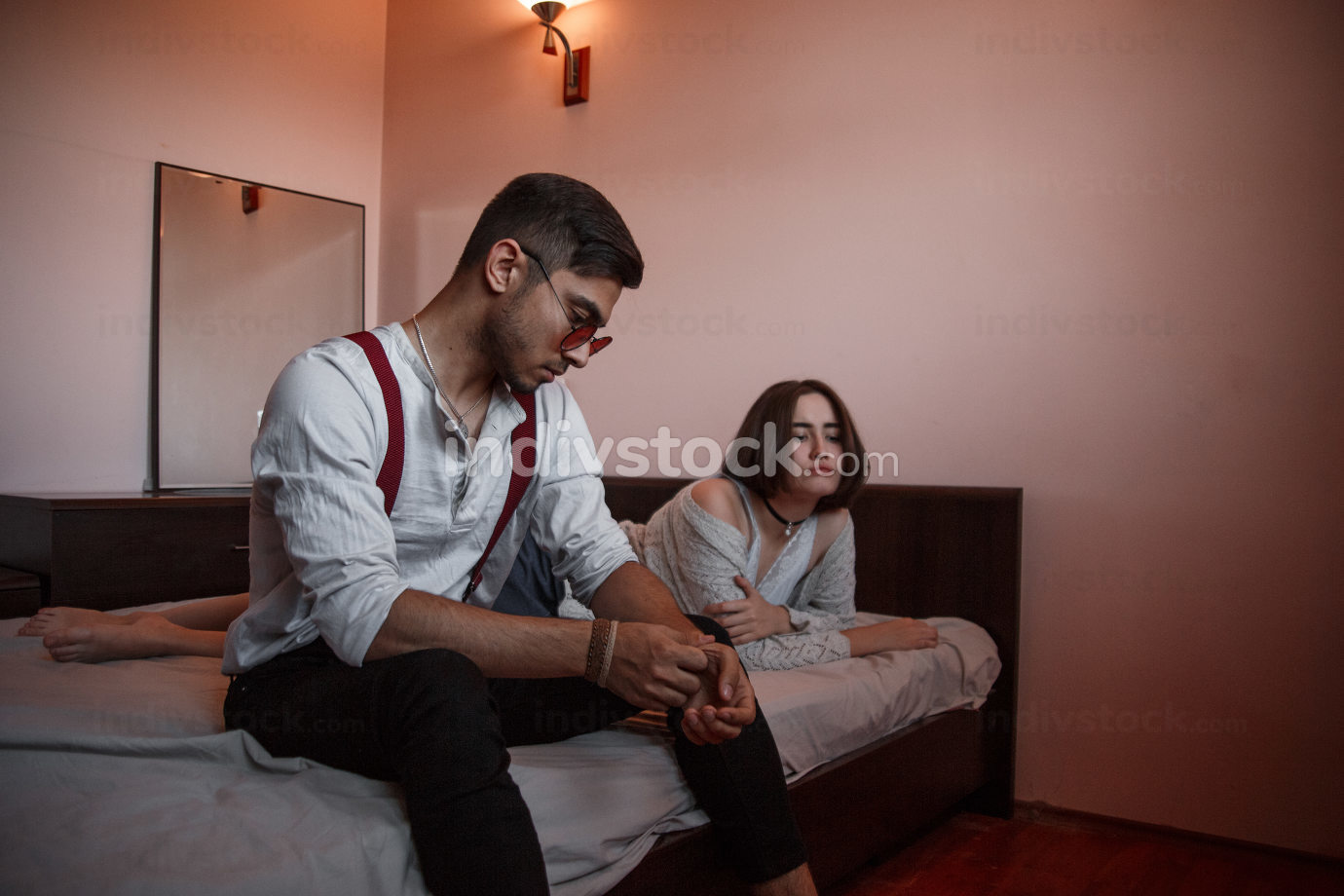a young stylish guy in glasses sits on the edge of the bed with a thoughtful sad face