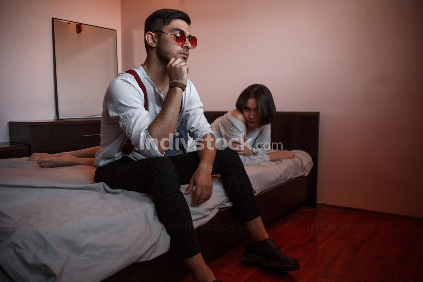 a young stylish guy in glasses sits on the edge of the bed with girl