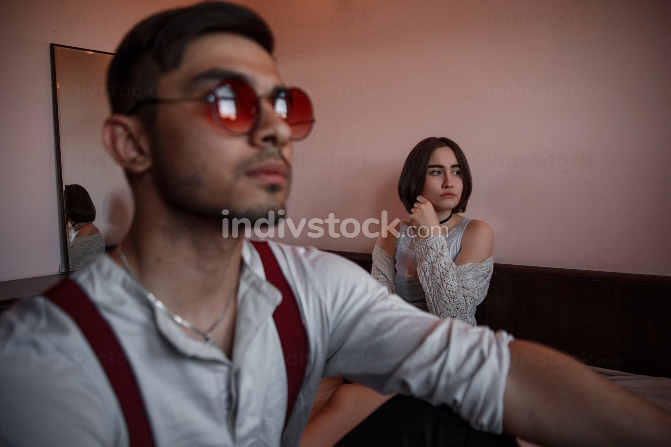 a young swarthy guy and a young brunette girl are sitting on the bed in the bedroom with sad faces