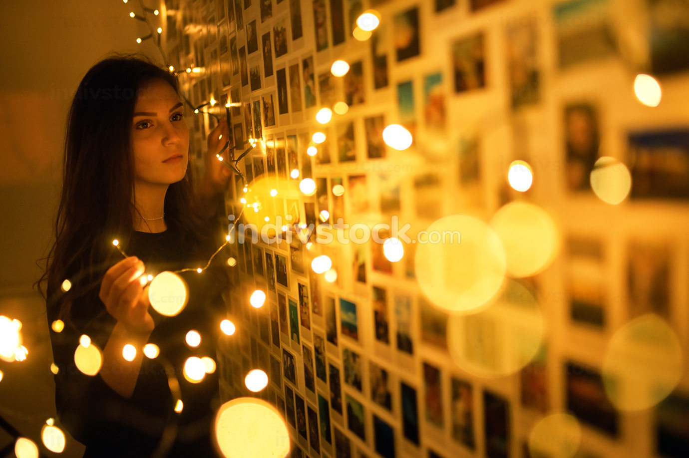 A Young Woman In Lights and Memories Photos on Wall