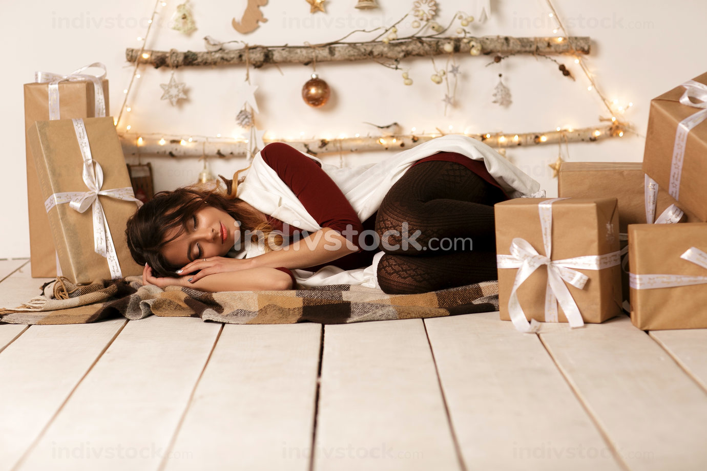 Adorable cute ittle girl sleeping under the Christmas tree by many Christmas gifts