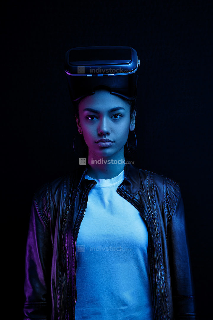 African-American girl in vr glasses with a virtual reality headset isolated on a black background, illuminated by neon lights