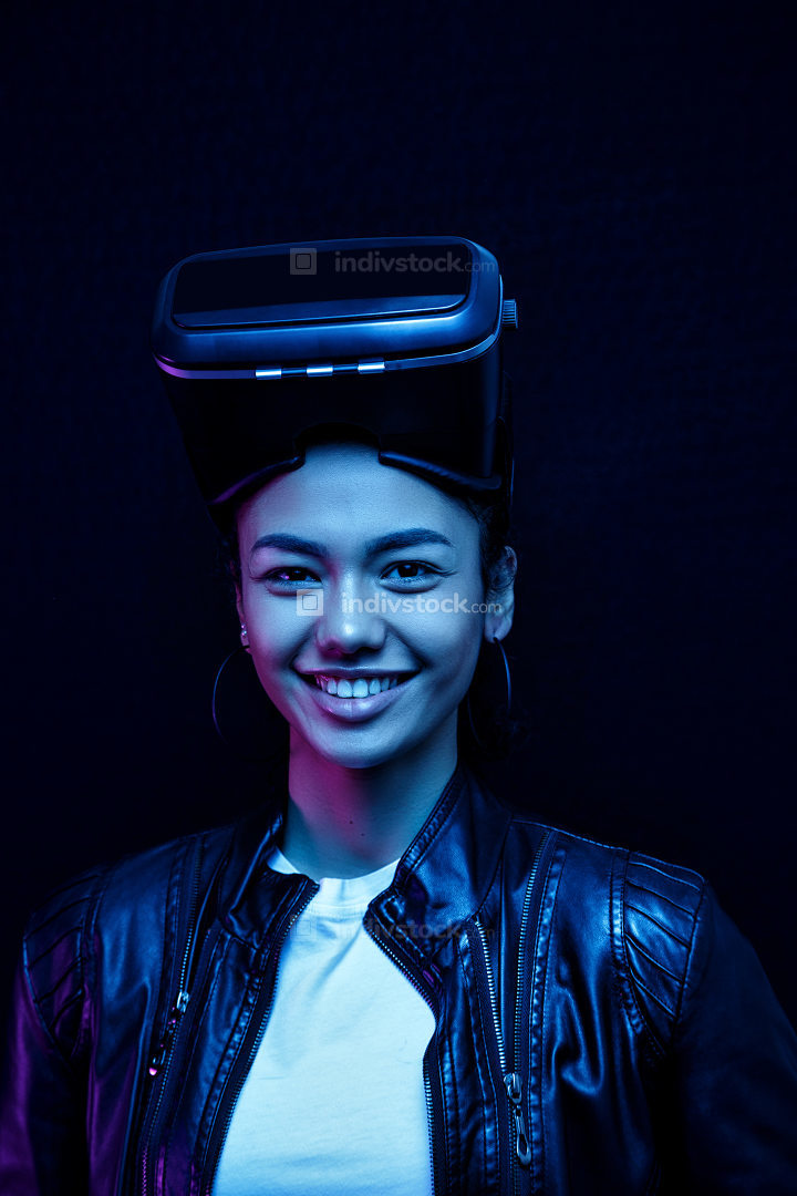 African-American smiling girl in vr glasses with a virtual reality headset isolated on a black background, illuminated by neon lights