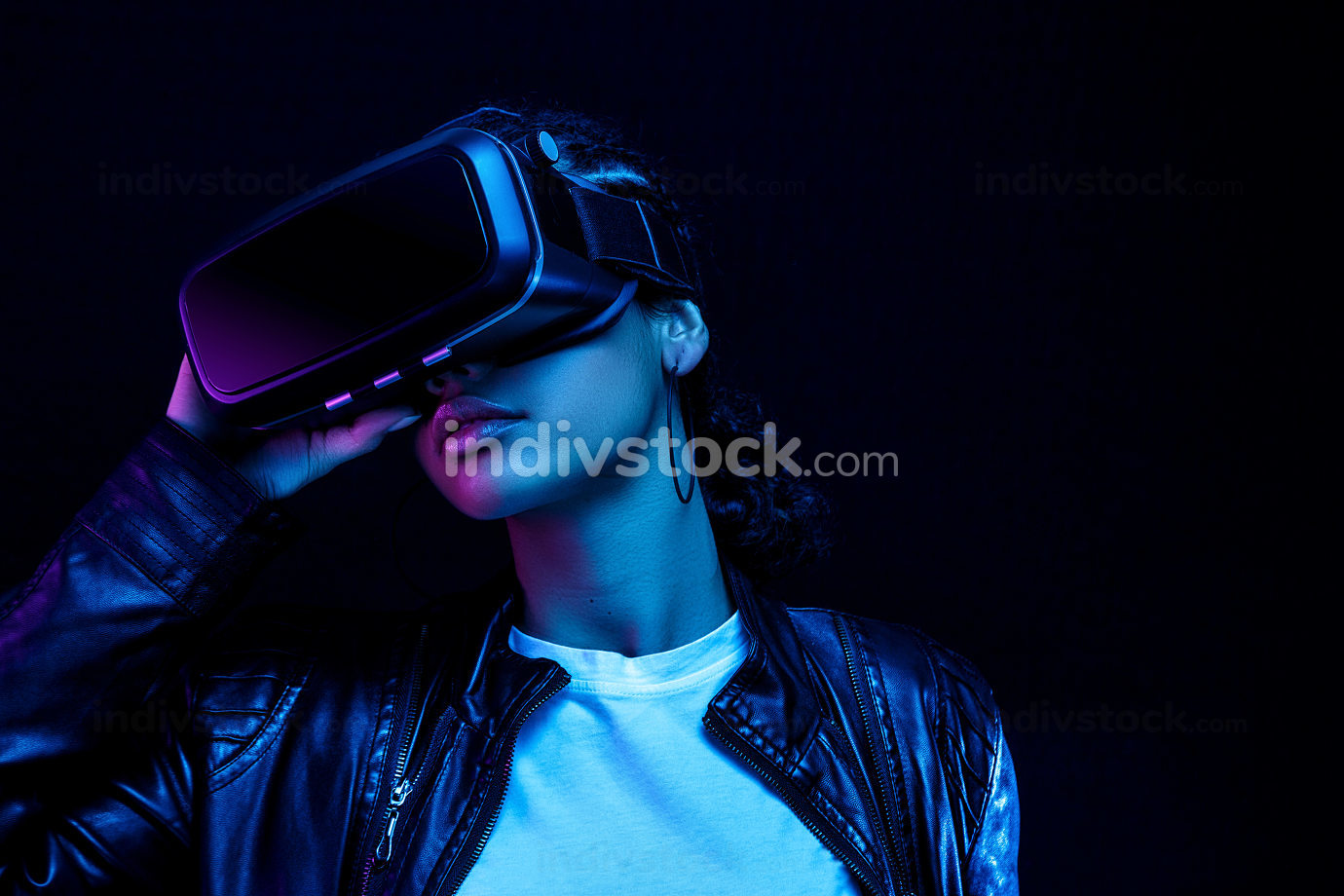 African-American young woman in vr glasses watching 360 degree video with a virtual reality headset isolated on a black background in neon light