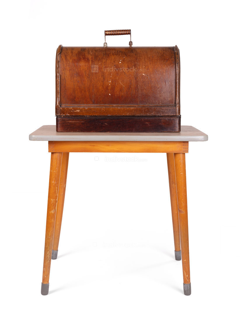 Antique, vintage sewing machine (wooden cover) on an old table