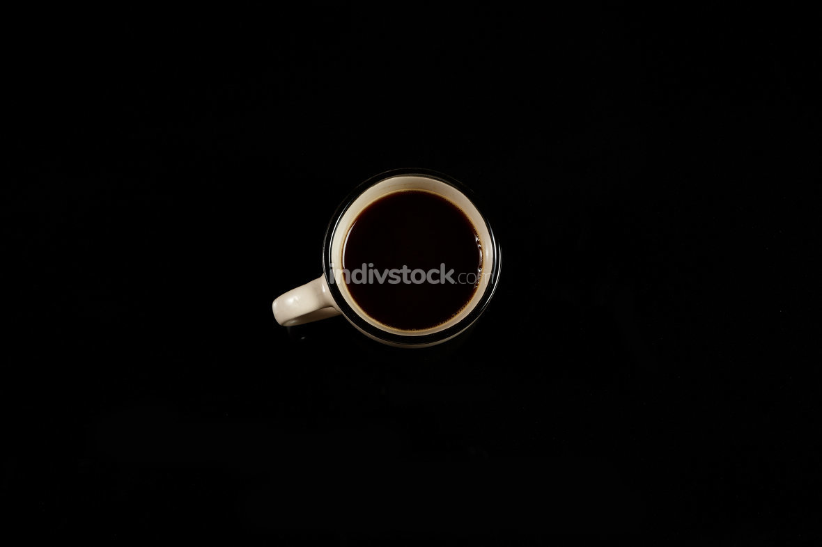 beige coffee Cup on a black isolated background. on black glass