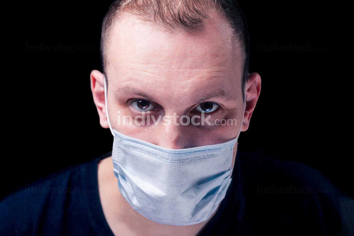 blonde man with brown eyes with a procedure medical white face mask from a coronavirus pandemic disease infection COVID-19 isolated on black background