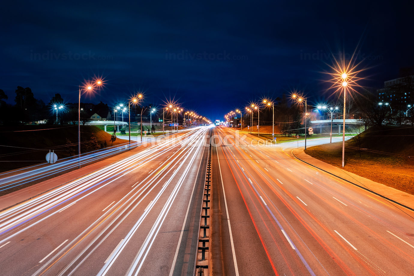bright lights from cars and street lamps on the highway at night