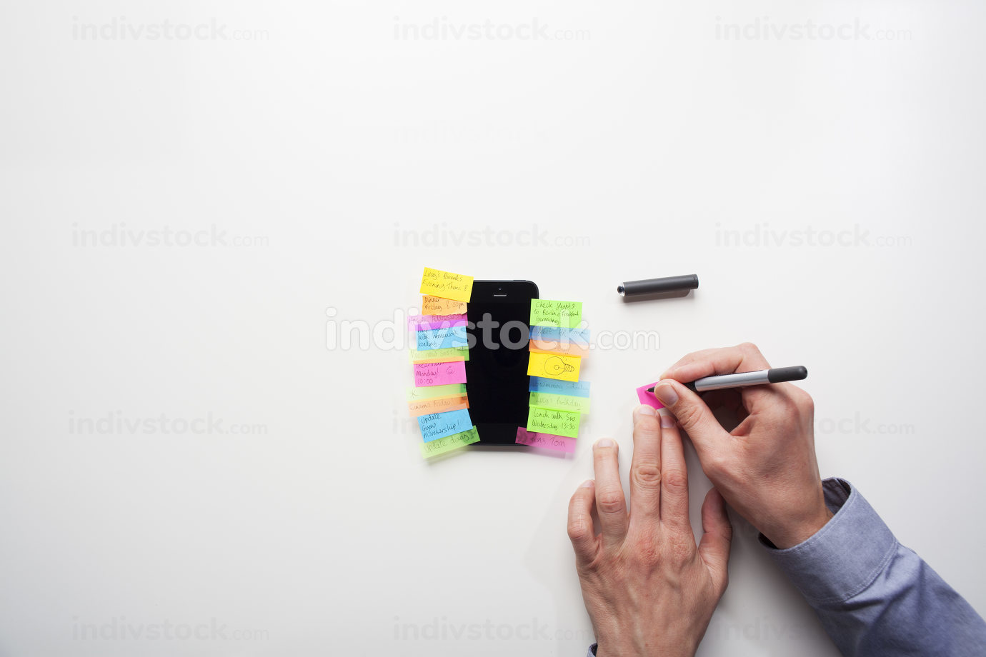 Businessman putting post it notes onto a smart phone
